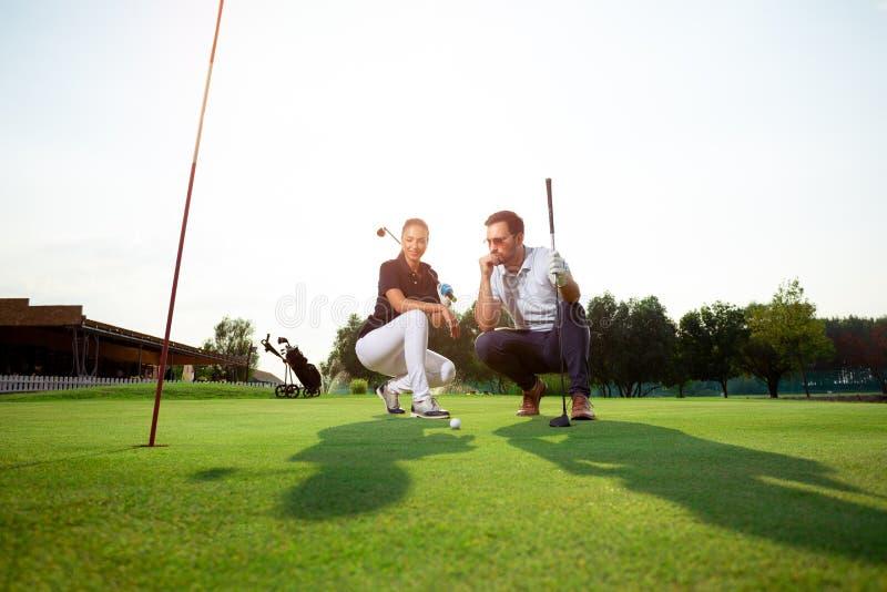 Pares desportivos novos que jogam o golfe em um campo de golfe fotos de stock