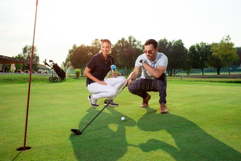 Pares desportivos novos que jogam o golfe em um campo de golfe foto de stock royalty free