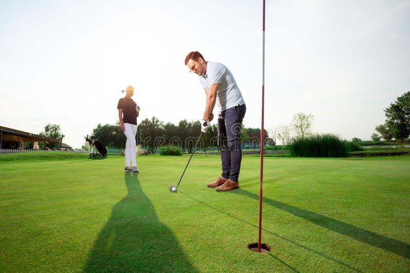 Pares desportivos novos que jogam o golfe em um campo de golfe imagem de stock royalty free
