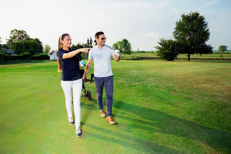 Pares desportivos novos que jogam o golfe em um campo de golfe imagem de stock