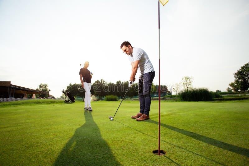 Pares desportivos novos que jogam o golfe em um campo de golfe - imagem fotografia de stock