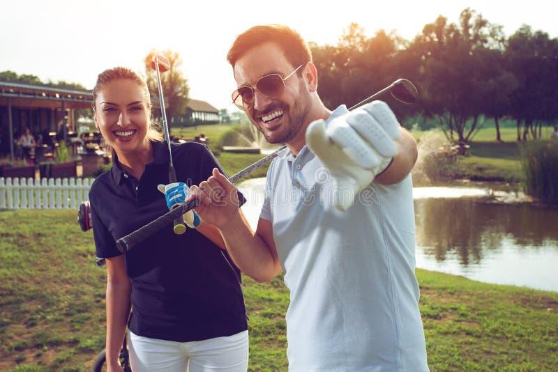 Pares desportivos novos que jogam o golfe em um campo de golfe fotografia de stock royalty free