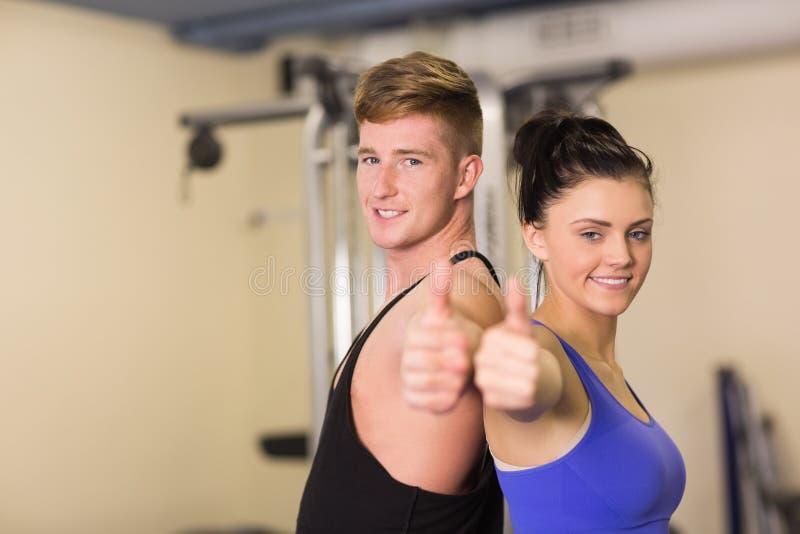 Pares desportivos que gesticulam os polegares acima no gym imagem de stock royalty free