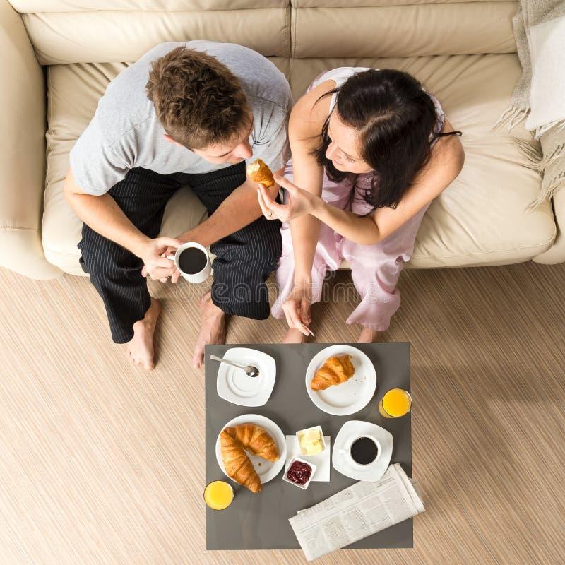 Pares despreocupados que comem o café da manhã junto fotografia de stock royalty free