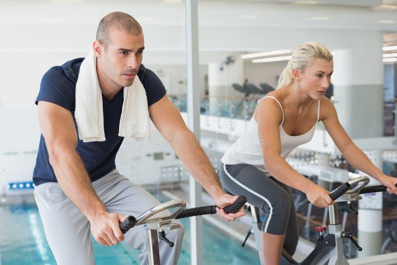 Pares determinados que trabalham em bicicletas de exercício no gym foto de stock