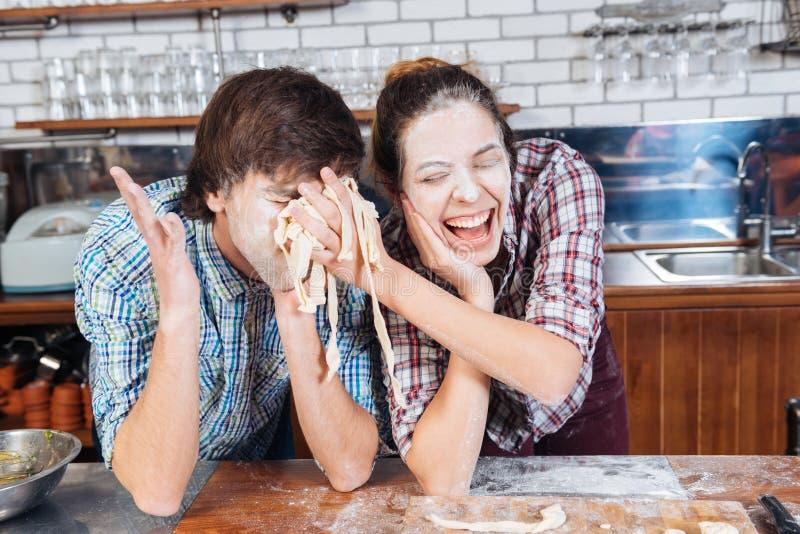 Pares divertidos con la harina en las caras que se divierten usando la pasta fotografía de archivo