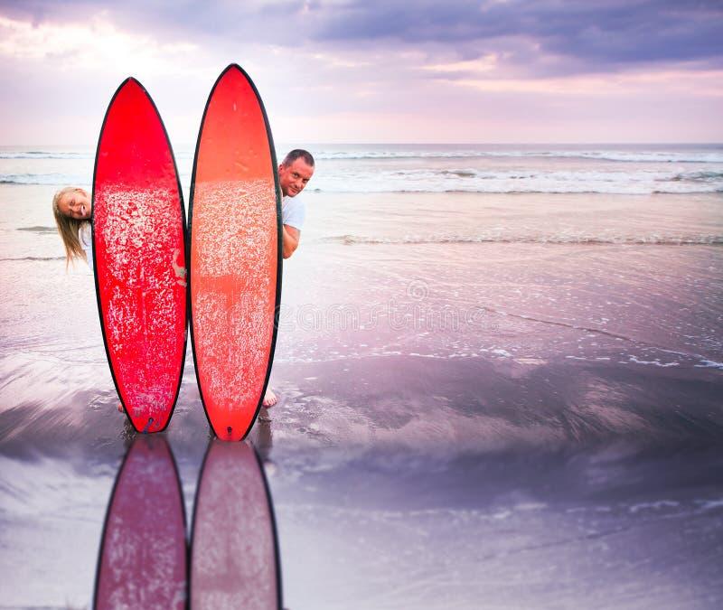 Pares divertidos de personas que practica surf en costa en Indonesia fotografía de archivo