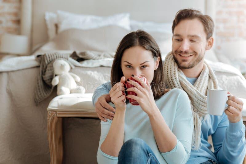 Pares divertidos engraçados que bebem o chá quente no quarto foto de stock royalty free