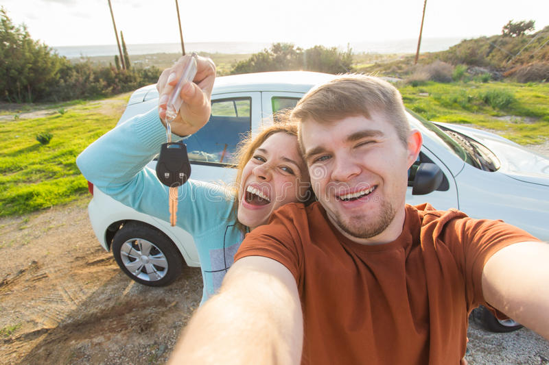 Pares divertidos jovenes con llaves al nuevo coche al aire libre imagenes de archivo