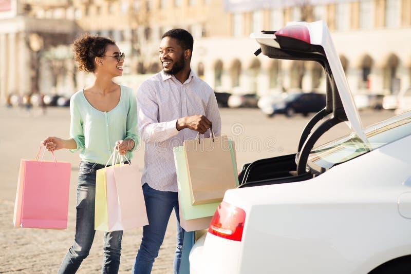 Pares do Afro após a compra na alameda que arranja sacos no carro imagem de stock