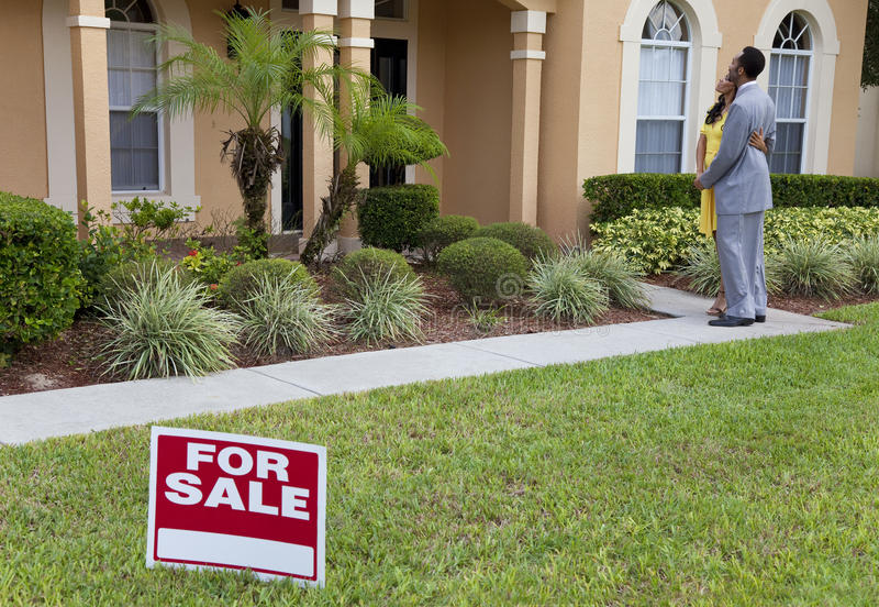 Pares do americano africano ao lado da casa para o sinal da venda fotos de stock