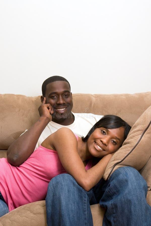 Pares do americano africano em sua sala de visitas imagens de stock royalty free