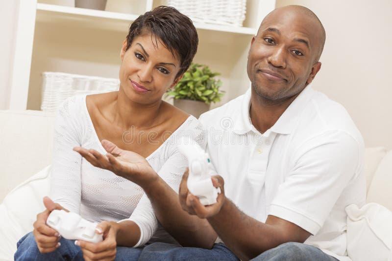 Pares do americano africano que jogam o jogo video do console foto de stock
