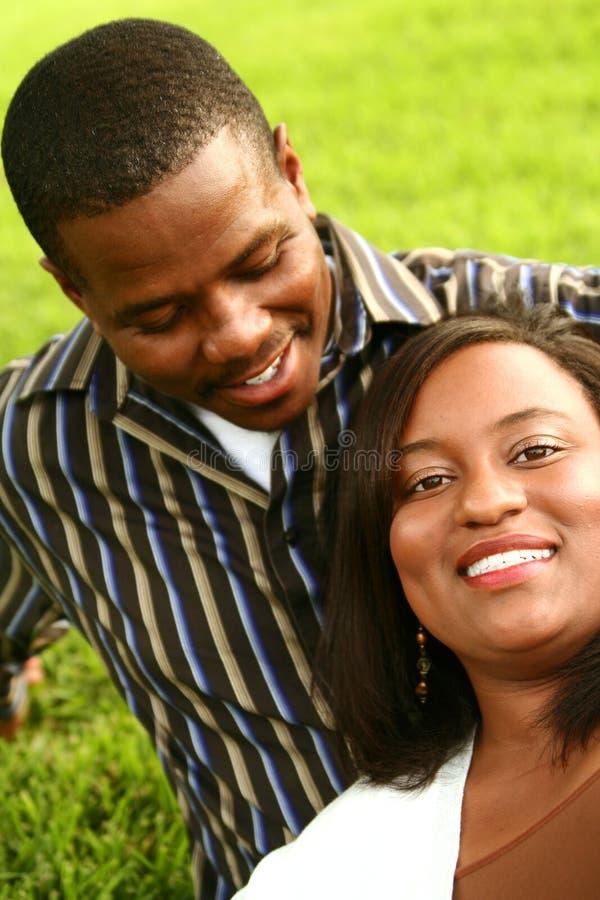Pares do americano africano que relaxam na grama fotografia de stock