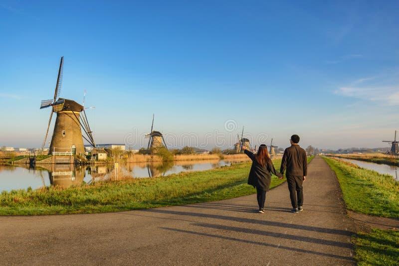 Pares do amor que andam com o moinho de vento holandês na vila de Kinderdijk fotografia de stock royalty free