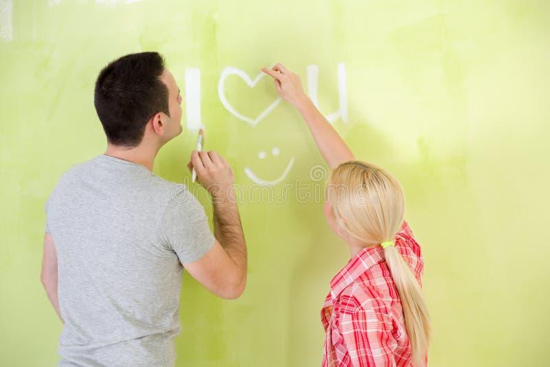 Pares do amor que pintam sua casa imagem de stock royalty free