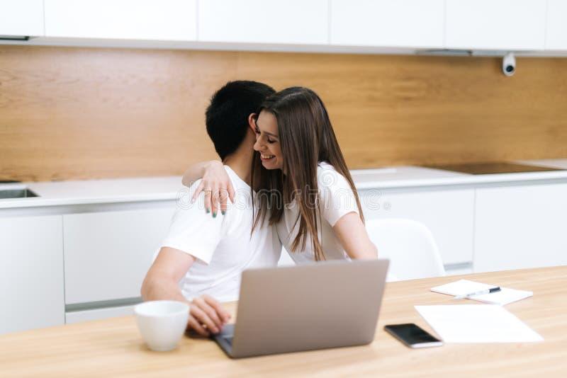 Pares do amor usando o port?til Computador em casa, mulher que abraça o homem, sorrindo fotografia de stock royalty free