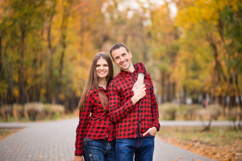 Pares do amor vestidos nas camisas vermelhas idênticas que abraçam na rua no parque do outono imagem de stock