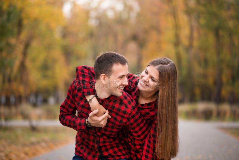 Pares do amor vestidos nas camisas vermelhas idênticas que abraçam na rua no parque do outono fotografia de stock royalty free