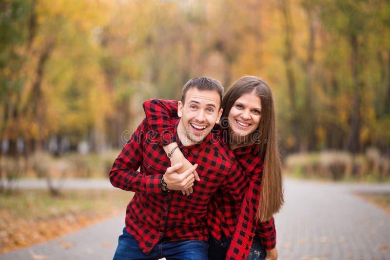 Pares do amor vestidos nas camisas vermelhas idênticas que abraçam na rua no parque do outono imagens de stock royalty free
