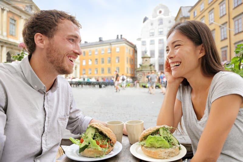 Pares do café que comem sanduíches do alimento em Éstocolmo fotos de stock royalty free
