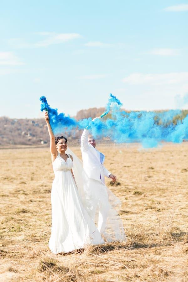 Pares do casamento com fumo azul no parque fotografia de stock