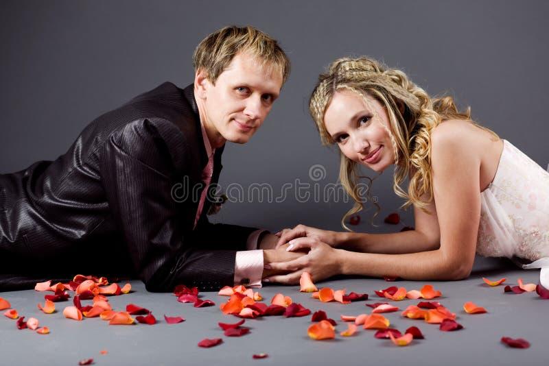 Pares do casamento entre as pétalas cor-de-rosa imagens de stock royalty free
