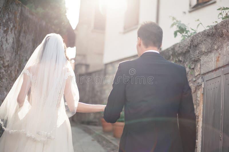 Pares do casamento que andam abaixo de uma rua imagens de stock
