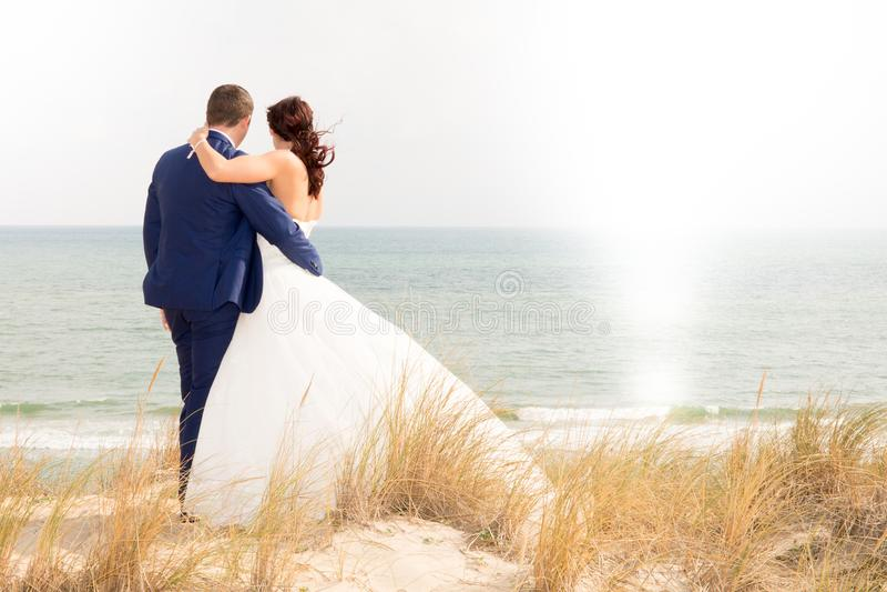 Pares do casamento que andam ao longo da praia ensolarada pela vista traseira foto de stock