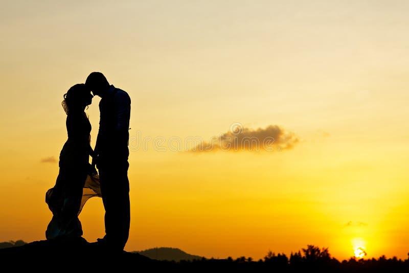Pares do casamento que beijam com por do sol foto de stock