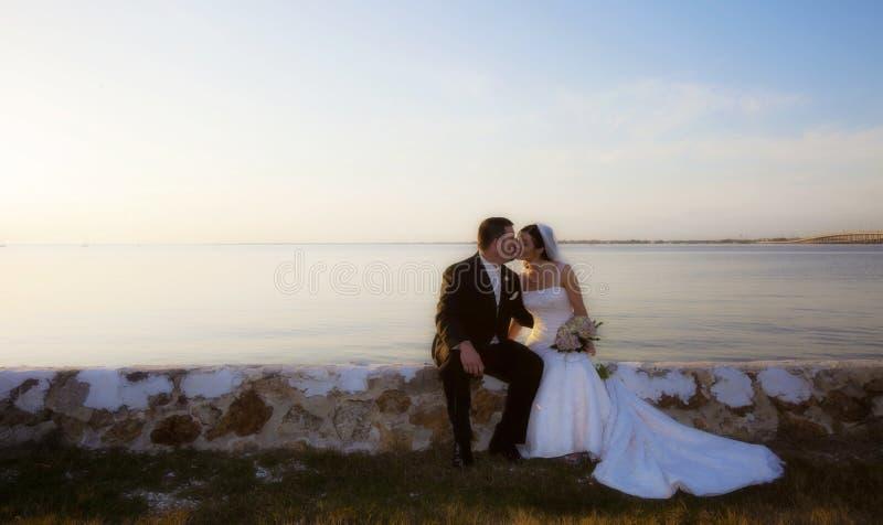Pares do casamento que beijam pela água fotografia de stock
