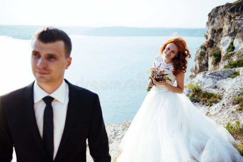 Pares do casamento que ficam sobre a paisagem bonita imagem de stock royalty free