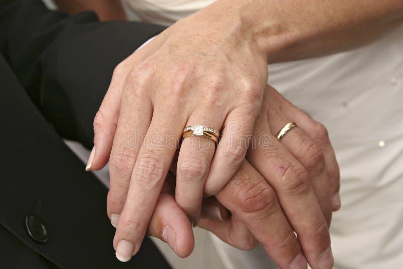 Pares do casamento que guardam as mãos, mostrando anéis imagens de stock