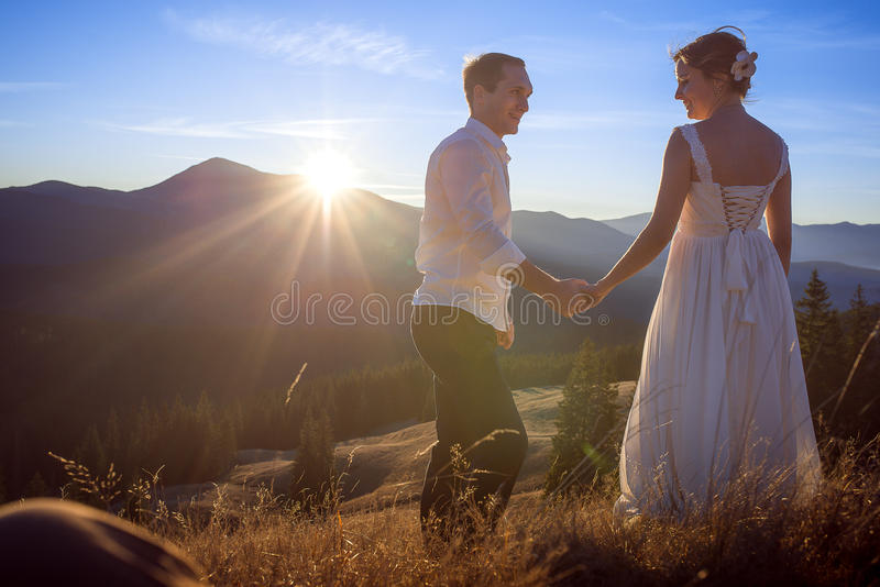 Pares do casamento que guardam levemente as mãos Por do sol nas montanhas fotos de stock