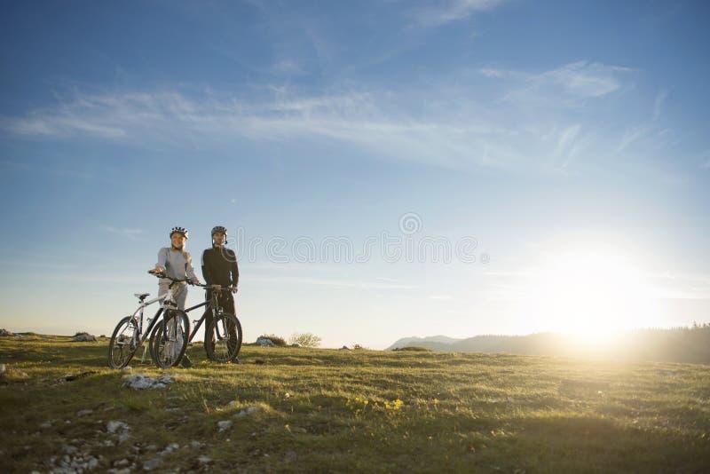 Pares do ciclista com os Mountain bike que estão no monte sob o céu da noite e que apreciam o sol brilhante no por do sol fotografia de stock royalty free