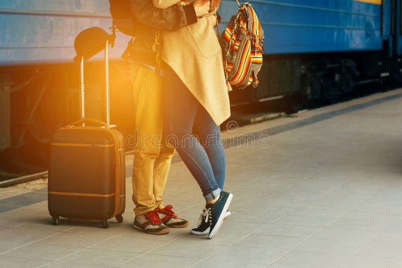 Pares do curso de amantes novos que beijam fora com o close up nos pés e nas sapatas Estação de caminhos-de-ferro no fundo Noite  foto de stock royalty free