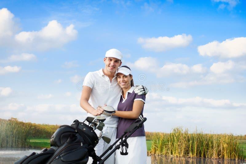 Pares do golfe com saco de golfe fotos de stock royalty free