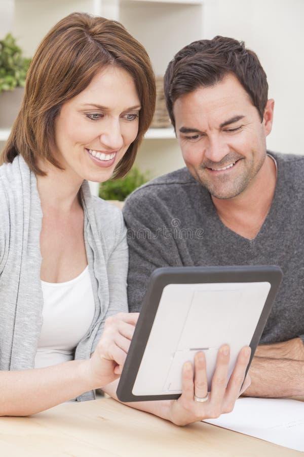 Pares do homem & da mulher no computador da tabuleta em casa imagem de stock royalty free