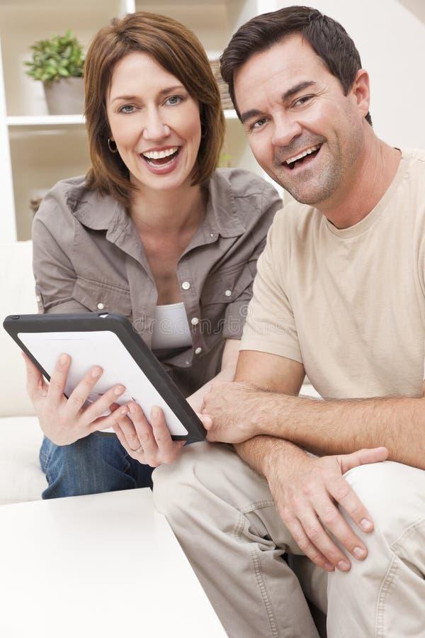 Pares do homem & da mulher usando o computador da tabuleta em casa fotos de stock