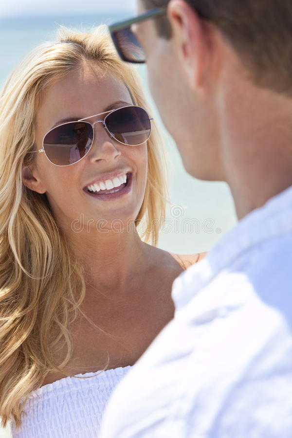 Pares do homem e da mulher nos óculos de sol na praia imagem de stock