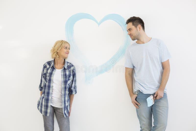 pares do Meados de-adulto que olham se com coração pintado na parede foto de stock