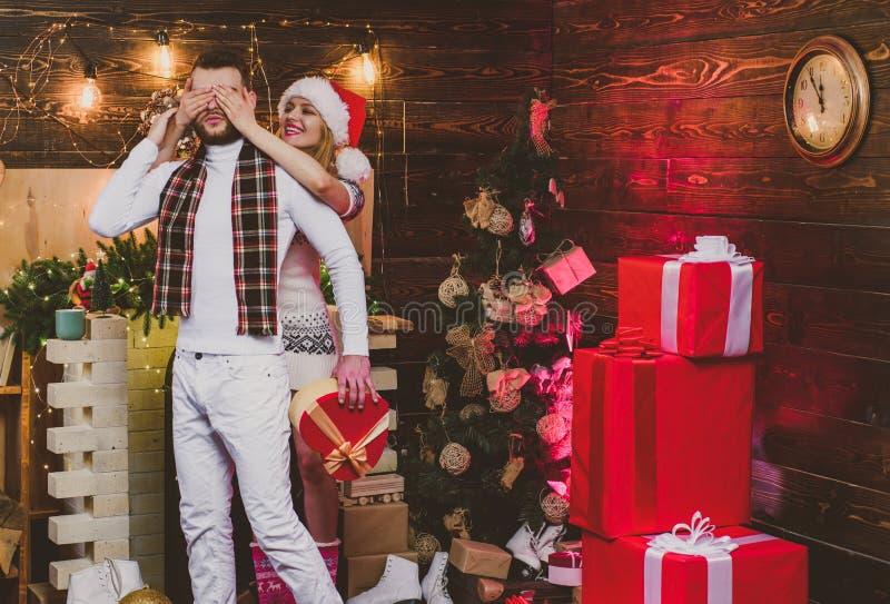 Pares do Natal no amor Pares felizes na sala de visitas, o Natal da caixa de presente dos noivos Close-up de um novo foto de stock