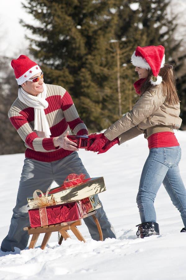 Pares Do Natal Que Jogam Com Os Presentes Na Neve Fotografia de Stock Royalty Free