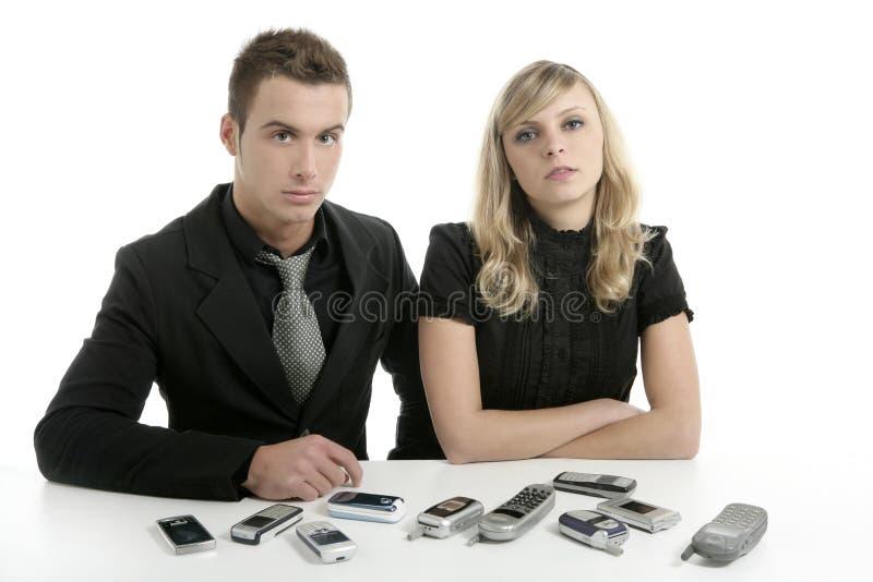 Pares do negócio com muitos telemóveis imagens de stock