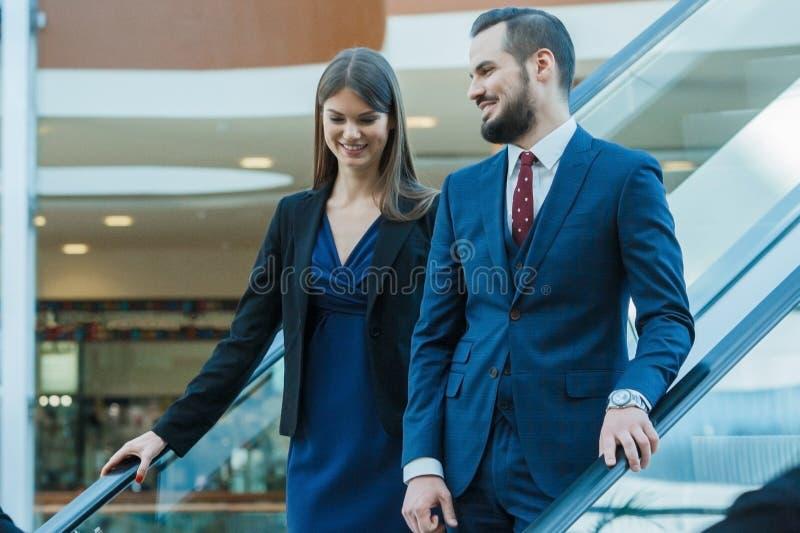 Pares do negócio na escada rolante foto de stock royalty free