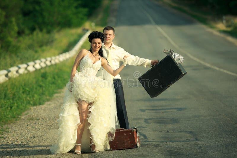 Pares do Newlywed que viajam em uma estrada imagem de stock