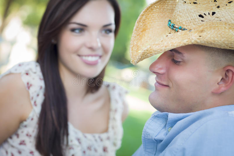 Pares do país da raça misturada com vaqueiro Hat Flirting no parque foto de stock