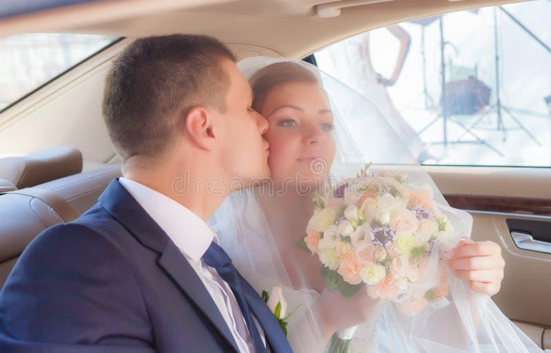 Pares do recém-casado que beijam-se no carro imagem de stock royalty free