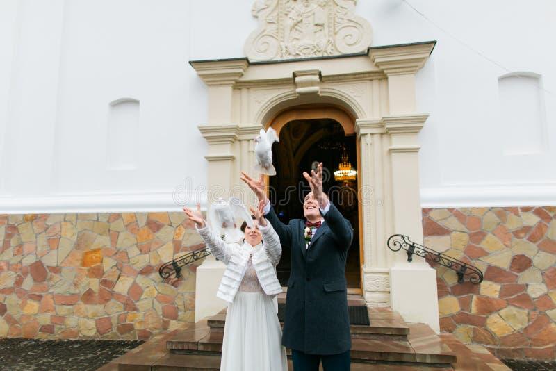 Pares do recém-casado que liberam pombas para voar ao sair da igreja após sua cerimônia de casamento imagem de stock