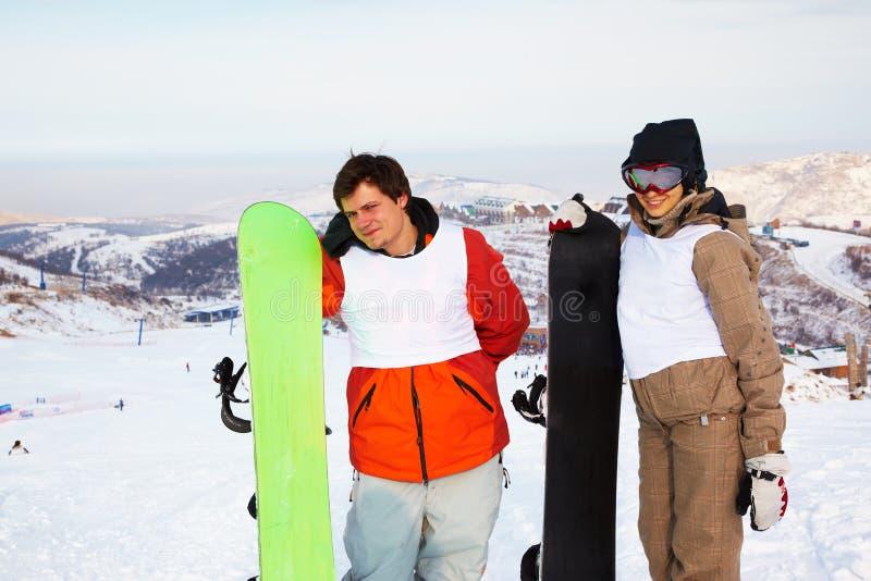 Pares do Snowboard na estância de esqui foto de stock
